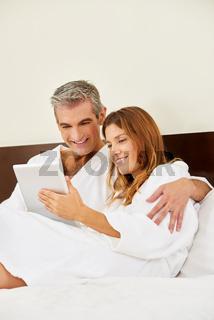 Paar im Hotel liest in einem Ebook