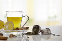 Green tea with cinnamonnd lemon and metallic strainer front view