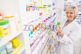 Smiling pharmacist holding prescription and medicine