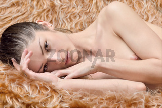 Beautiful naked woman with naked breast is laying .