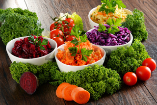 Composition with four vegetable salad bowls on wooden table.