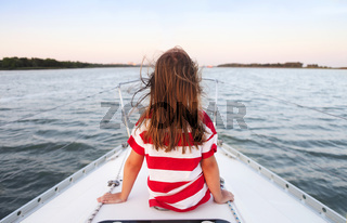 Little girl enjoying ride on yacht at sunset