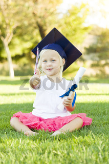 Little Girl In Grass Wearing Graduation Cap Holding Diploma With Ribbon