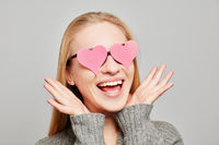 Erstaunte Frau mit rosa Herzen vor Augen