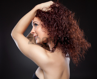 Beautiful young woman with red curly hair