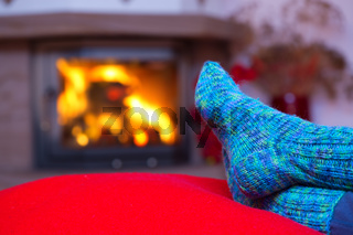 Feet in woollen blue socks by the fireplace.