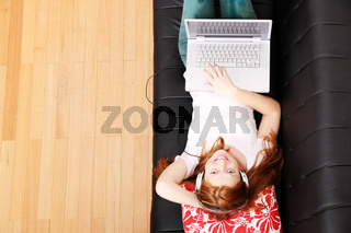 Young Redhead Girl surfing on the Sofa