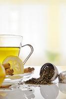 Green tea with cinnamonnd lemon and metallic strainer close up