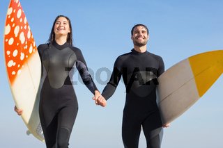happy couple in wetsuits with surfboard on a sunny day