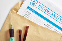 Blood report in envelope with vials and syringe with blood