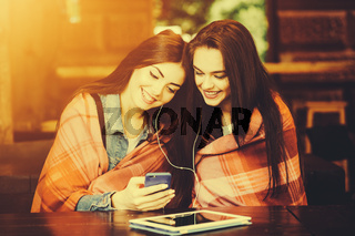 Two girl sitting listening to music