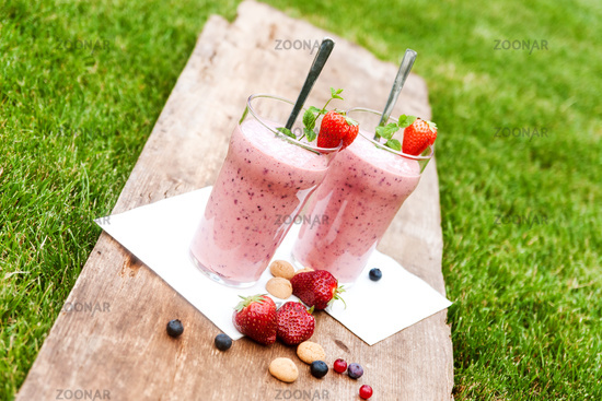 2 glasses with a berry milkshake and decoration on