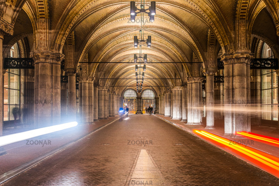 Cyclists ride  through Rijksmuseum arch at night. Amsterdam, Netherlands, Europe