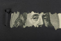Benjamin Franklin macro peeking through torn black paper