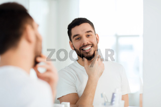 happy young man looking to mirror at home bathroom