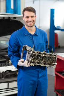 Smiling mechanic holding an engine