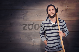 Composite image of portrait of hipster with hooded shirt holding axe