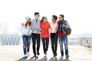 happy teenage friends walking along city street