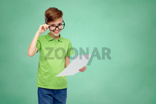 happy boy in eyeglasses holding school test result