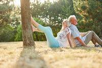 Senioren Paar sitzt Rücken an Rücken im Gras