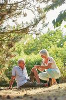 Frau hilft altem Mann mit Knieverletzung