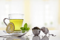 Green tea with mint and lemon with strainer front view