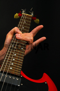 Hand with red guitar and devil horns isolated on black