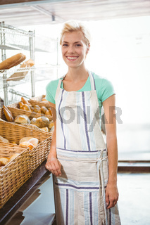Smiling waitress posing next basket of bread