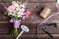 Rustic bouquet from gillyflowers and alstroemeria on old wooden background with wooden heart and scissors
