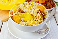 Pilaf fruit with pumpkin in bowl and spoon on board