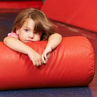 Mädchen liegt auf Kissen in Turnhalle