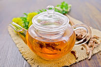 Tea of Rhodiola rosea in glass teapot on board