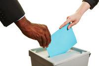 Hände halten Stimmzettel an Wahlurne