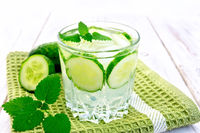 Lemonade with cucumber and mint in glassful on board