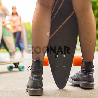 Teenage girl urban long board riding.