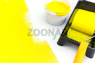 can of yellow paint with paint roller and tray