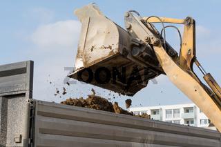 Schaufellader kippt Erde von Baustelle in Tieflader - Nahaufnahme