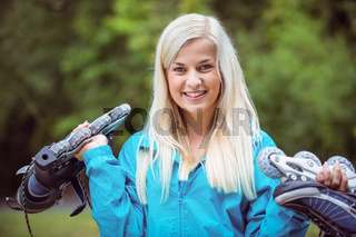 Happy blonde holding inline skates