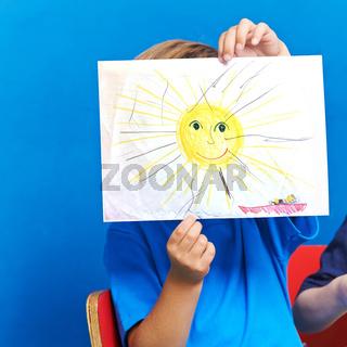 Kind zeigt Sonne und Meer auf Papier