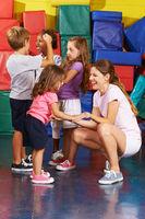 Kinder turnen mit Erzieherin in Turnhalle
