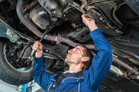 Mechanic checking the condition of a lifted car