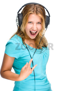 Beautiful girl with headphones show rock symbol isolated on white