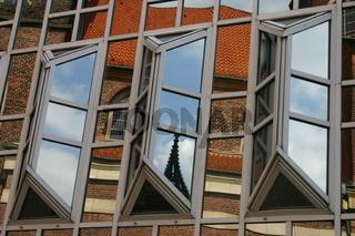 Kirchturmspiegelung in einer Kaufhausfassade in Münster