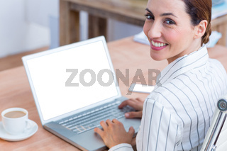 Brunette businesswoman smiling using laptop