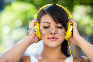 Athletic woman wearing yellow headphones and enjoying music with eyes closed