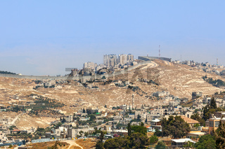 Palestinian village and town separated by wall.