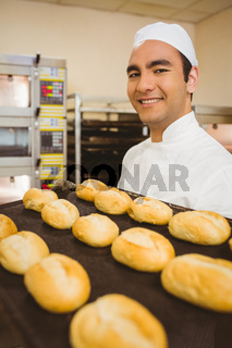 Baker smiling at camera holding tray of rolls