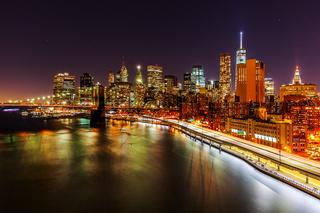 Skyline von Downtown Manhattan mit Brooklyn Bridge and East River in NYC bei Nacht