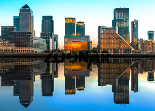 Canary Wharf with mirrored reflections in the warm evening sun, London, United Kingdom