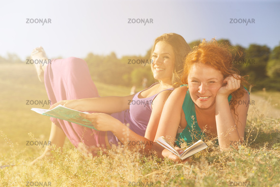 Two women read on grass